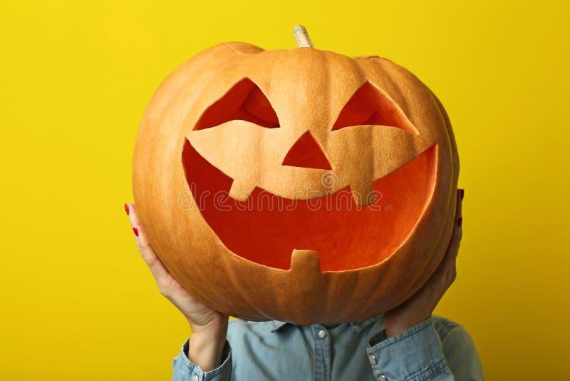 Hands holding halloween pumpkin. Female hands holding halloween pumpkin on yellow background stock image