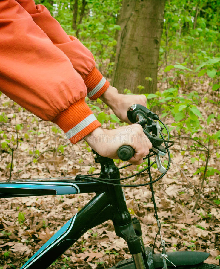 Hands in holding handlebar of a bicycle stock images