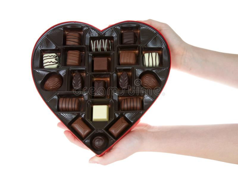 Hands holding heart box with chocolate candies, isolated. Hands holding Heart shaped box with chocolate candies isolated on white background. A popular gift for royalty free stock photo