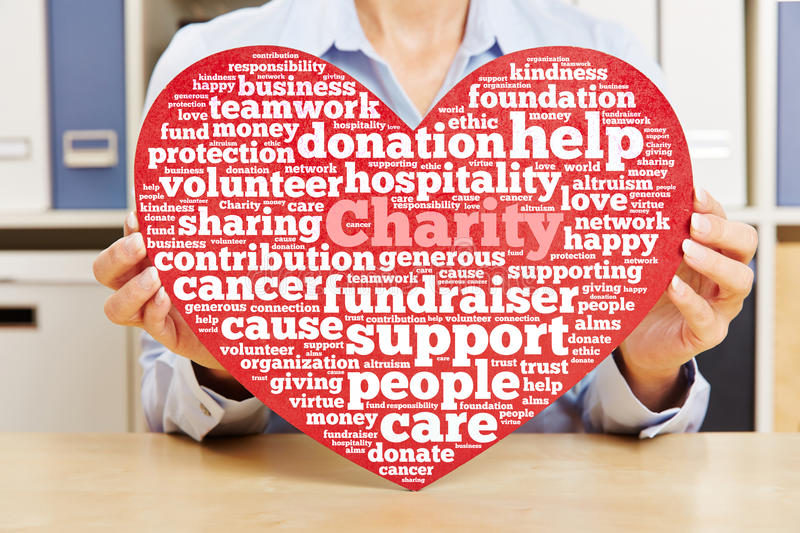 Hands holding heart with charity tag cloud stock images