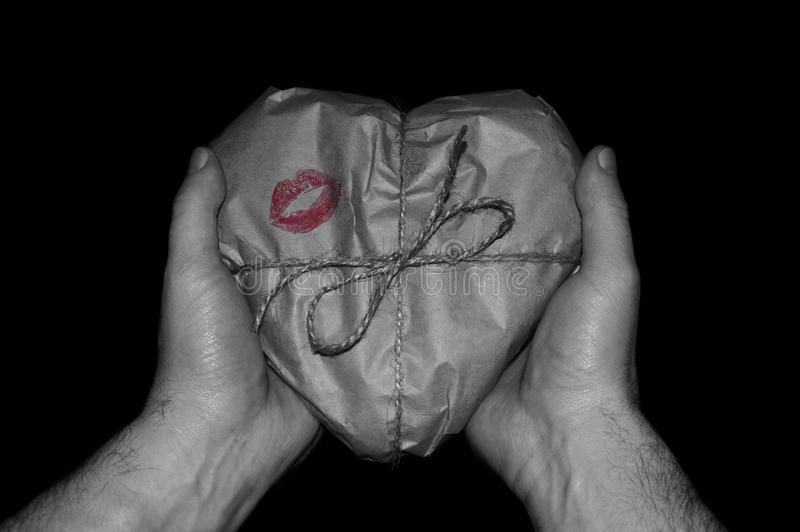 Hands holding a heart-shaped gift wrapped in paper. royalty free stock image