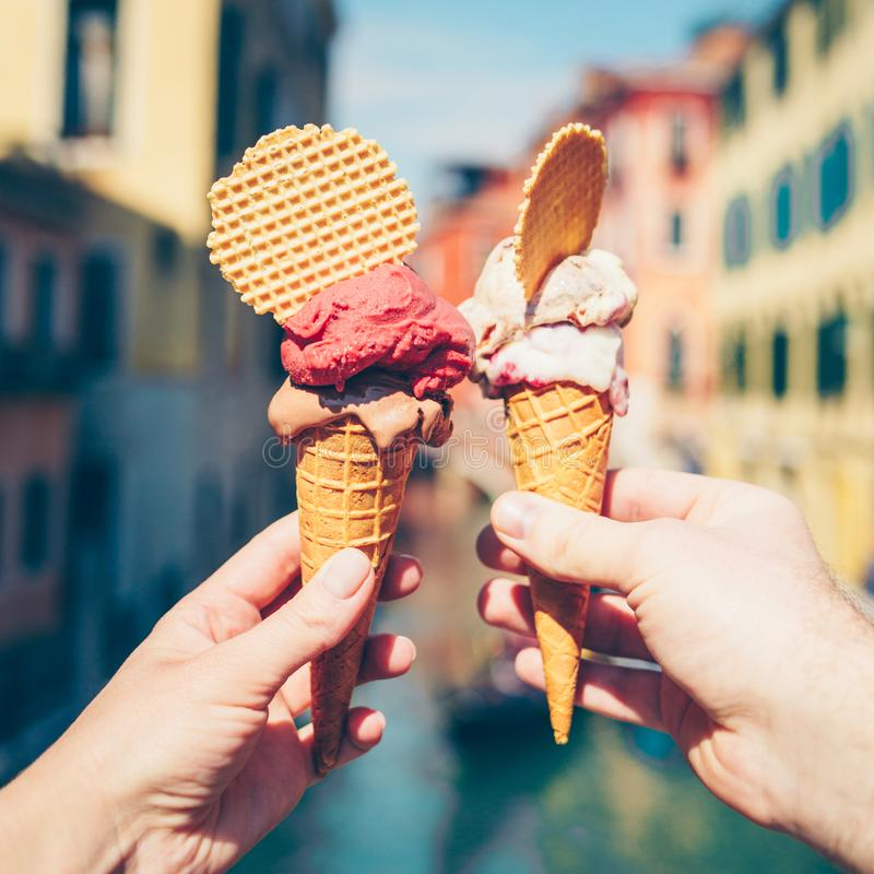 Hands holding ice cream in waffle cone. royalty free stock photography