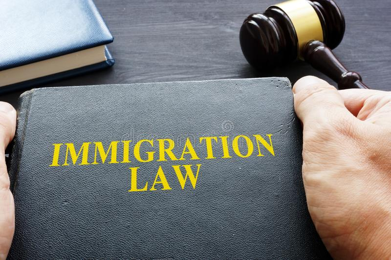 Hands are holding Immigration Law book. Hands are holding Immigration Law book concept royalty free stock photo