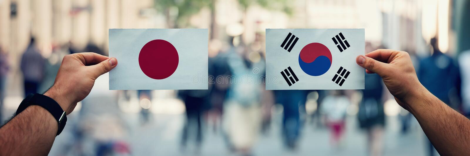 Hands holding Japan and South Korea flags as trade dispute on politics arena, overcrowded street. Diplomacy and future strategy,. Relations between countries royalty free stock image