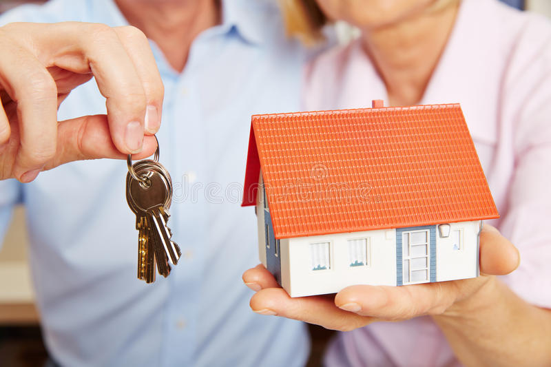Hands holding key and house. Two hands of a senior couple holding keys and a little house stock images