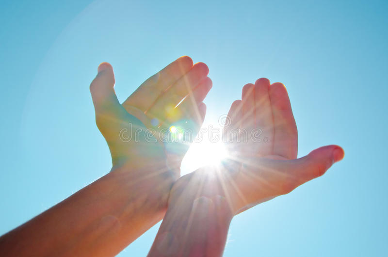 Hands holding light. Hands offering light over a white background. Hands holding the sun with the blue sky background