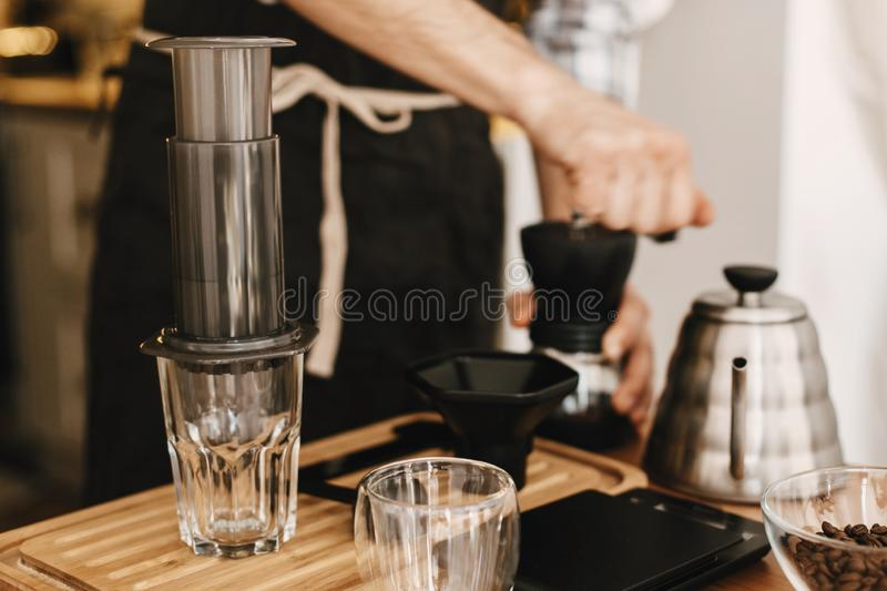 Hands holding manual grinder and aeropress, scales, coffee beans, kettle, glas cup on wooden table. Professional barista grinding stock photography