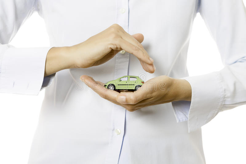 Hands holding a miniature car. Hands of a business woman holding a green toy car on a white background royalty free stock image