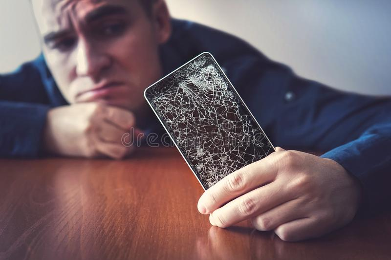 Hands holding a mobile phone with a broken screen over the wooden surface stock images