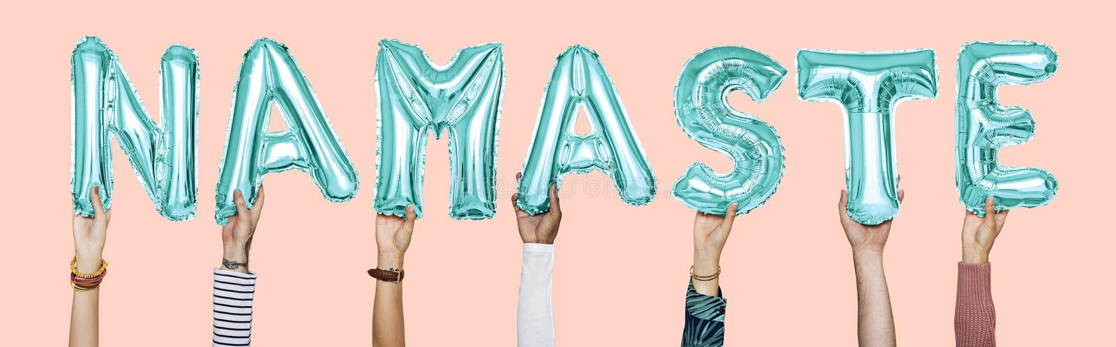 Hands holding namaste word in balloon letters stock photography