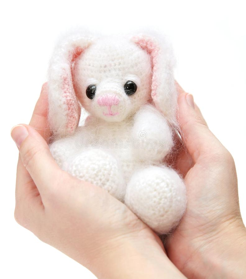 Hands Holding Newborn Toy Hare With Caress Stock Photography