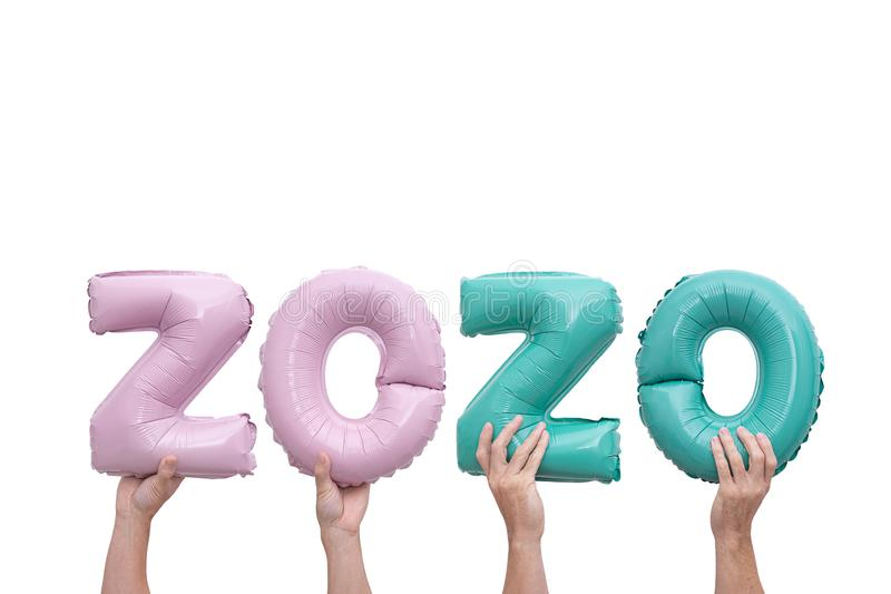Hands holding numbers numbers 2020 made of pink and mint foil balloons on pink background. Hands holding numbers 2020 made of pink and mint foil balloons on pink royalty free stock photography