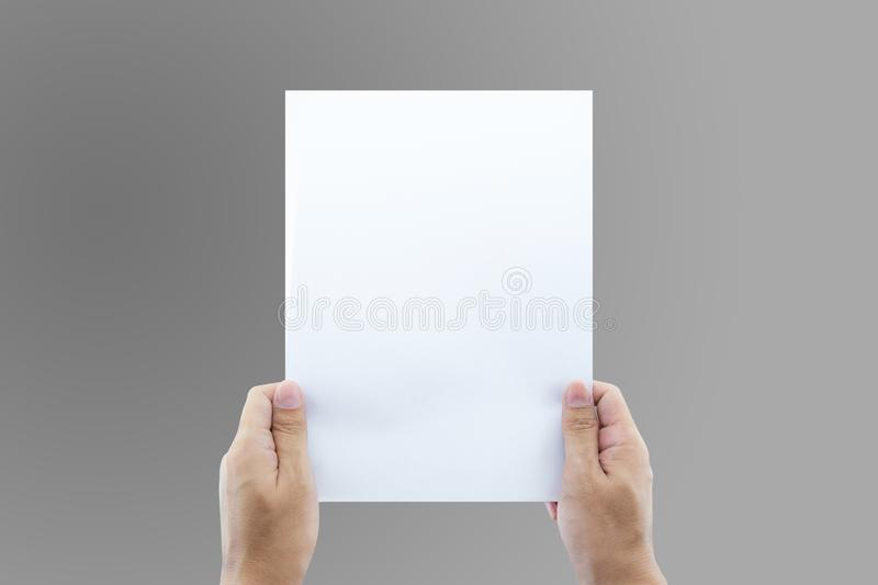 Hands holding paper blank a4 size for letter paper. The hands holding paper blank a4 size for letter paper stock image