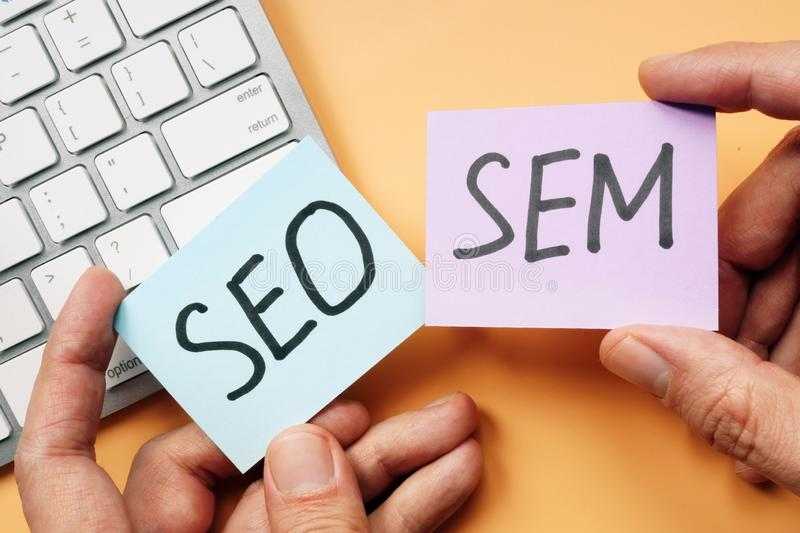 Hands holding cards with SEO and SEM stock images