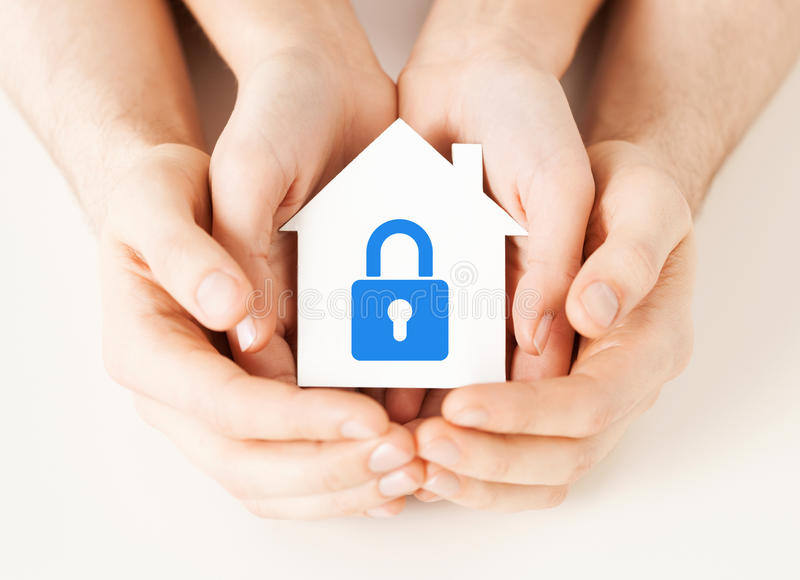 Hands holding paper house with lock royalty free stock image