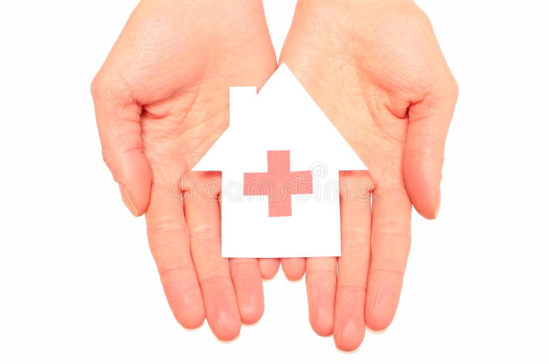 Hands holding paper house with red cross sign. Concept for medicine and healthcare for family royalty free stock image