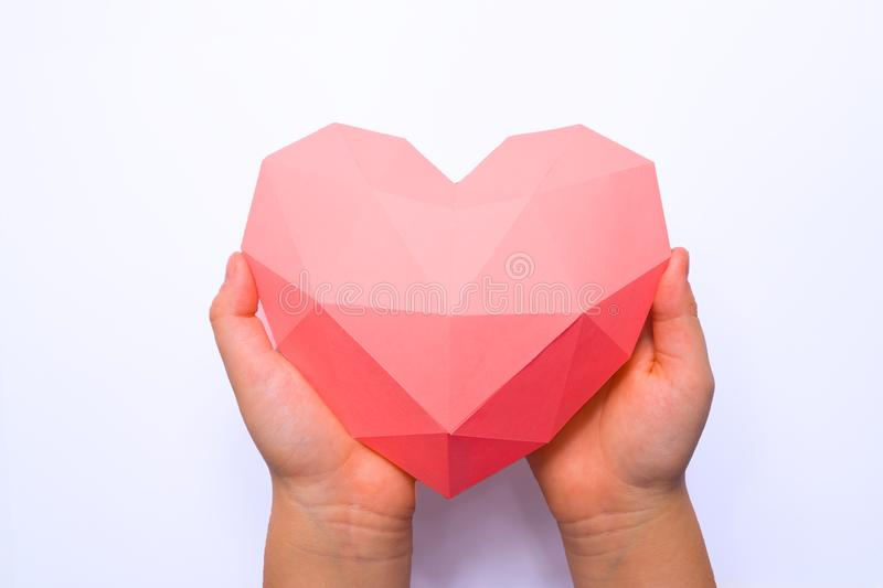Hands holding a paper polygonal pink heart. On white background royalty free stock photos