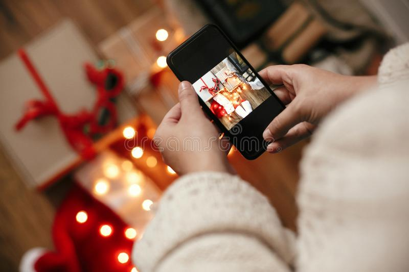 Hands holding phone and taking photo of christmas gift boxes, santa hat, illumination lights on wooden background in dark room. Stylish hipster girl in sweater royalty free stock photography