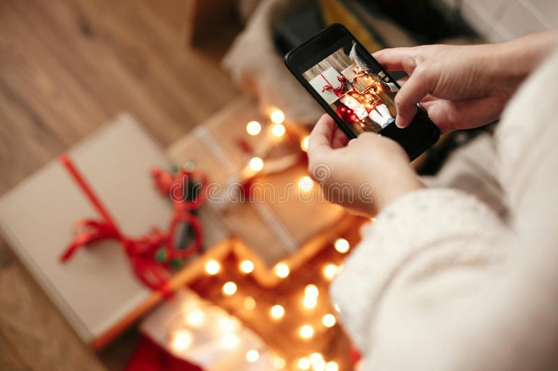 Hands holding phone and taking photo of christmas gift boxes, santa hat, illumination lights on wooden background in dark room. Stylish hipster girl in sweater stock image