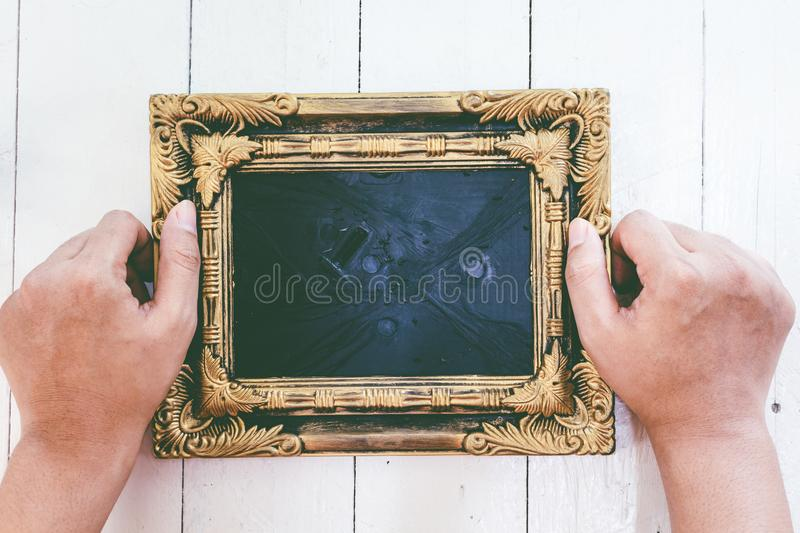 Hands holding picture frame on wooden background stock photo