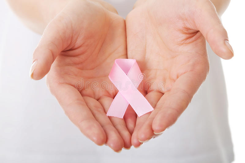 Hands holding pink breast cancer awareness ribbon royalty free stock photography