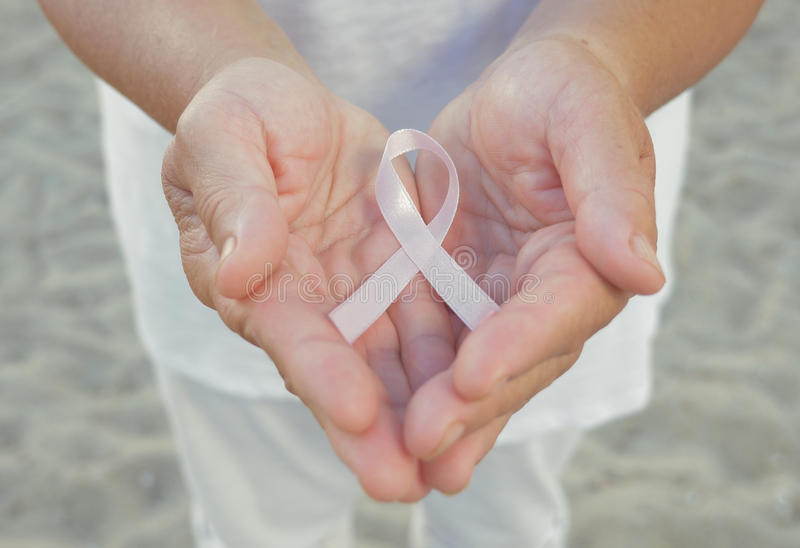 Hands holding pink ribbon royalty free stock image