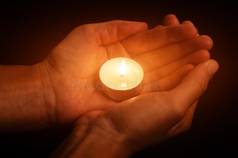 Hands holding and protecting glowing lit or burning candle candlelight on darkness. Black background. Concept for prayer, praying, hope, vigil, night watch stock images