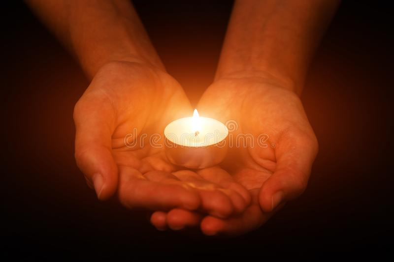 Hands holding and protecting glowing lit or burning candle candlelight on darkness. Black background. Concept for prayer, praying, hope, vigil, night watch stock photos