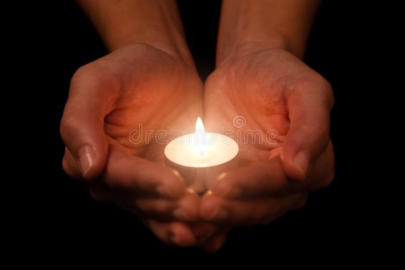 Hands holding and protecting lit or burning candle candlelight on darkness. Black background. Concept for prayer, praying, hope, vigil, night watch stock photography