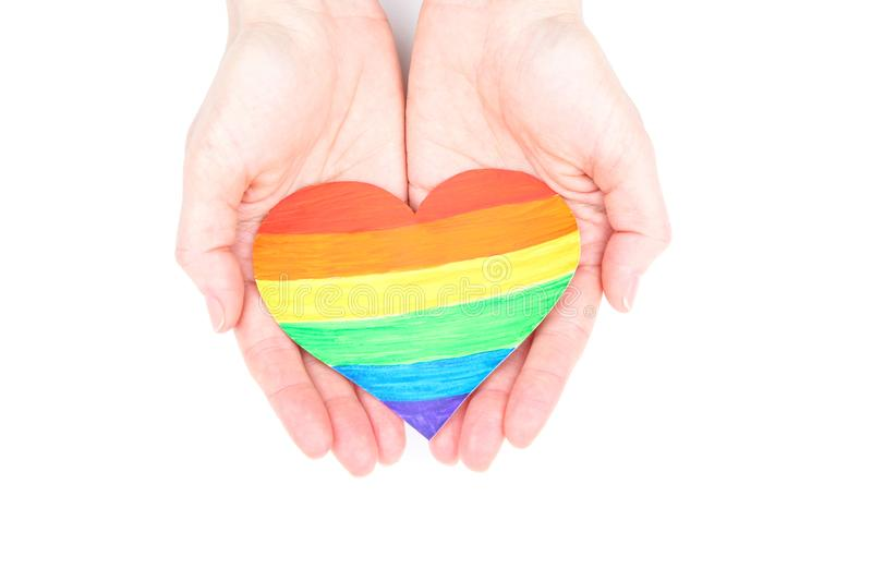 Hands holding rainbow paper heart stock images