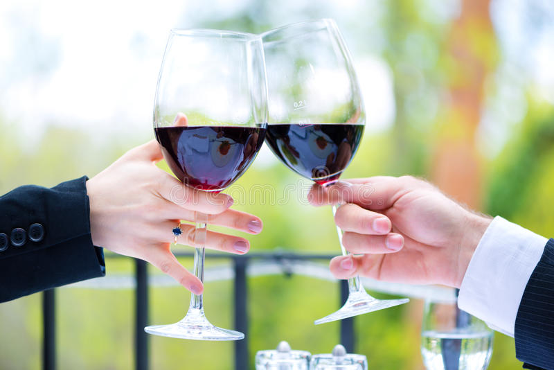 Download Hands Holding Red Wine Glasses To Clink Stock Photo - Image: 32187996