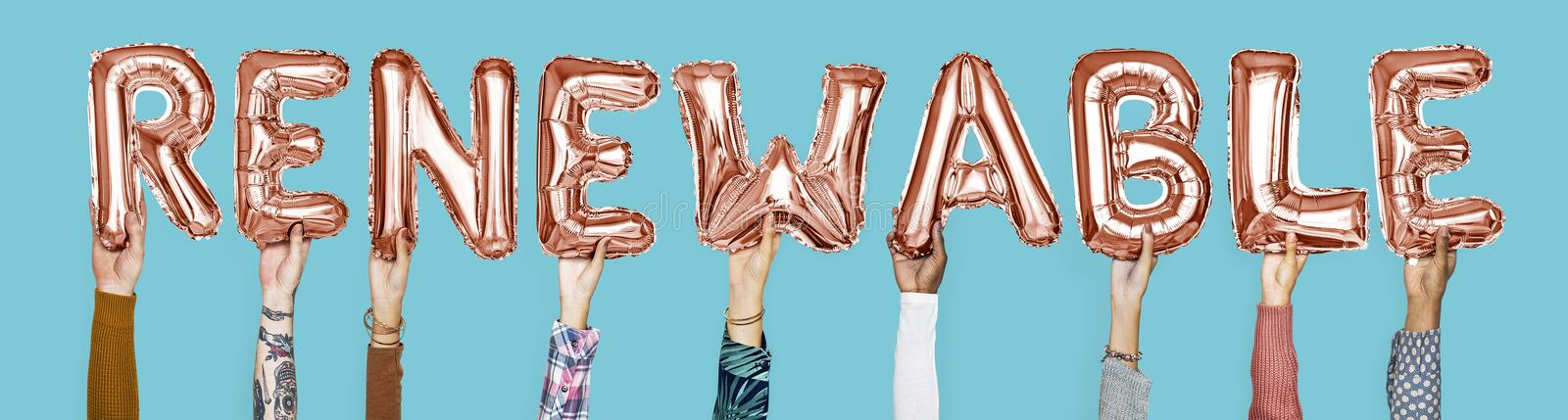 Hands holding renewable word in balloon letters stock image