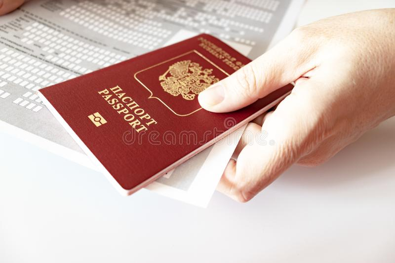 Hands holding russian passport and registration at the place of stay form royalty free stock images