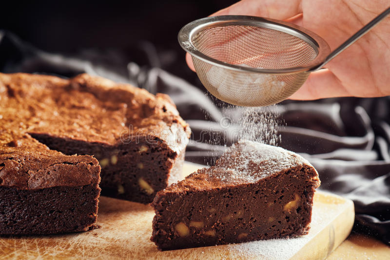 Hands holding sieve with powdered sugar and sprinkling cake. Hands holding sieve with white powdered sugar and sprinkling the powder on piece of freshly baked royalty free stock images