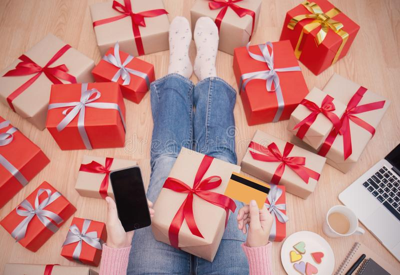 Hands holding smartphone and credit card with Christmas gift box top view stock photo