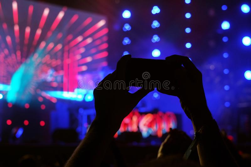 Hands holding smartphone on the festival concert. royalty free stock photography