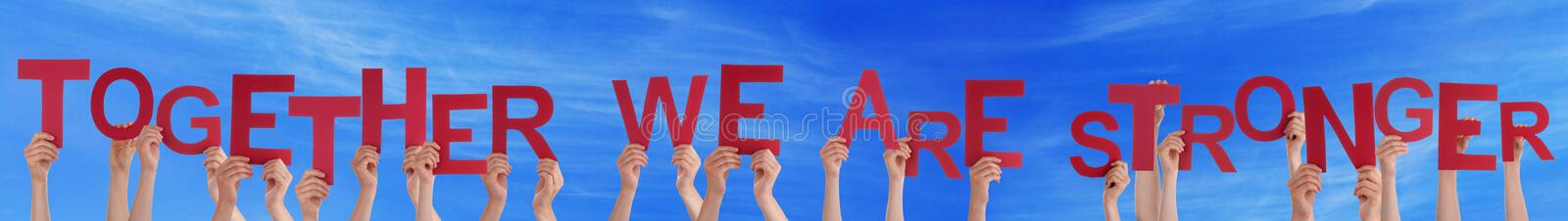 Hands Holding Straight Word Together We Are Stronger Blue Sky. Many Caucasian People And Hands Holding Red Straight Letters Or Characters Building The English royalty free stock images