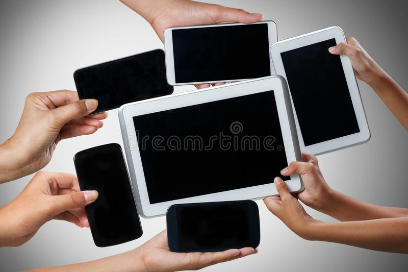 Hands holding tablet computer and mobile phone in different ways royalty free stock image
