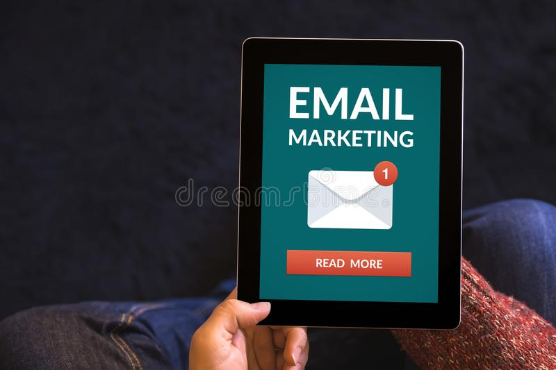 Hands holding tablet with email marketing concept on screen. Hands holding digital tablet computer with email marketing concept on screen. All screen content is royalty free stock photography