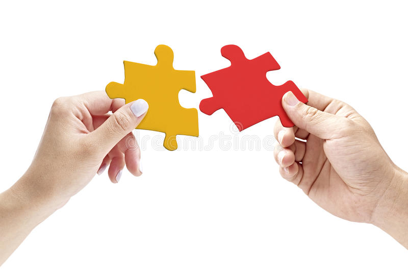 Hands holding two matching jigsaw pieces royalty free stock images
