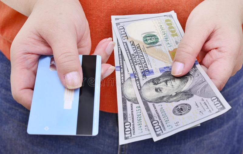 Hands holding us dollar bills and credit card. stock photos
