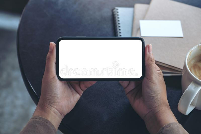 Hands holding and using a black mobile phone with blank screen horizontally for watching with coffee cup and notebooks on table. Top view mockup image of hands stock photography