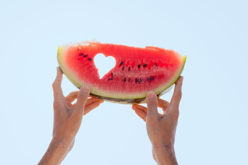 Hands holding a watermelon slice with heart center towards the sky. Hands holding a watermelon slice with cutted hole as a shape of heart, center towards the sky royalty free stock photography