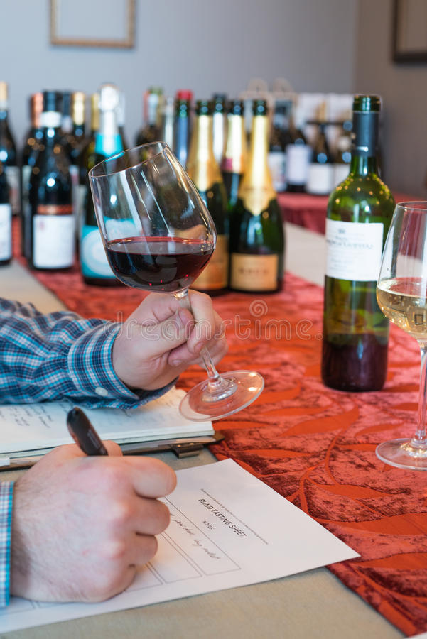 Hands Holding a Wineglass and Pen for Wine Tasting. Some person's hands, one holding a glass of wine and one with a pen writing on a tasting form, during wine stock photos