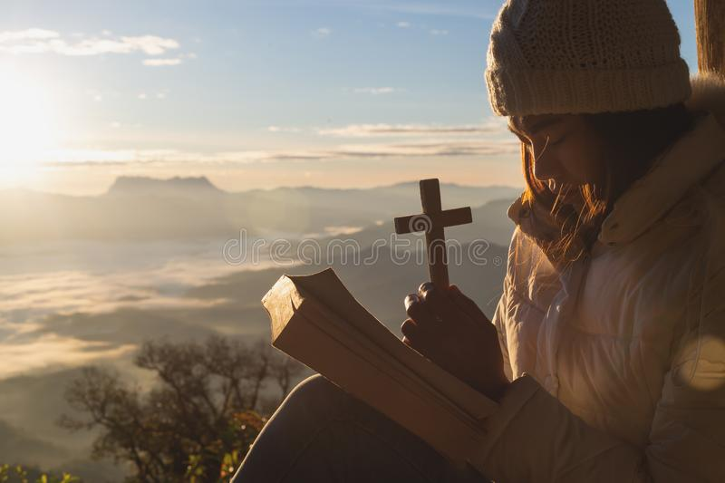 Hands holding wooden cross over open holy bible on the mountain background with morning sunrise, spirtuality and religion, stock photo
