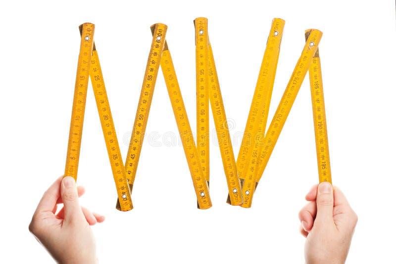 Hands holding wooden folding ruler stock photo