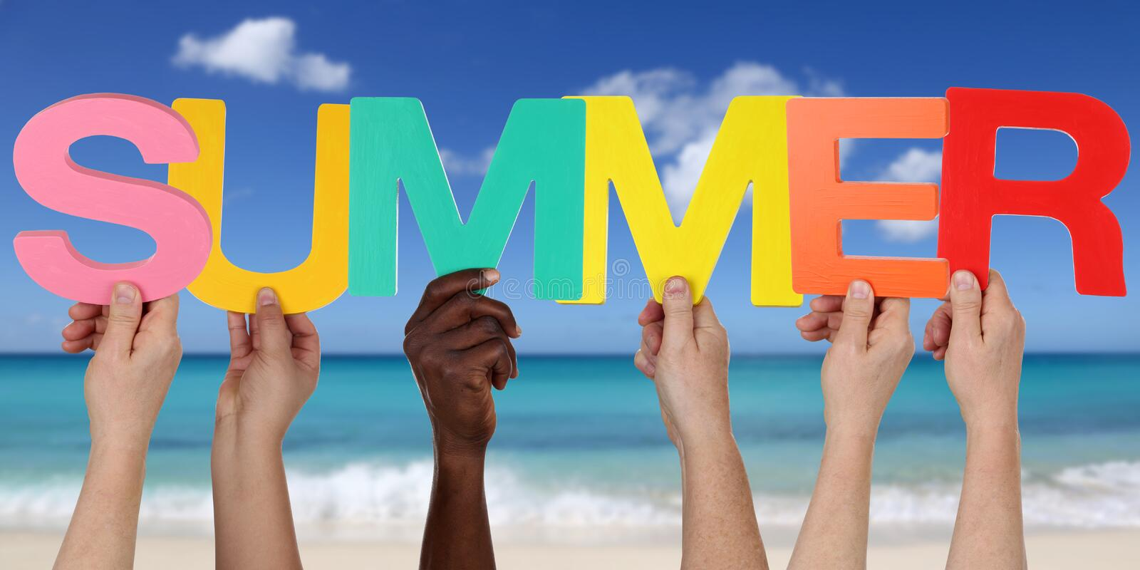 Hands holding the word summer on beach in vacation stock image