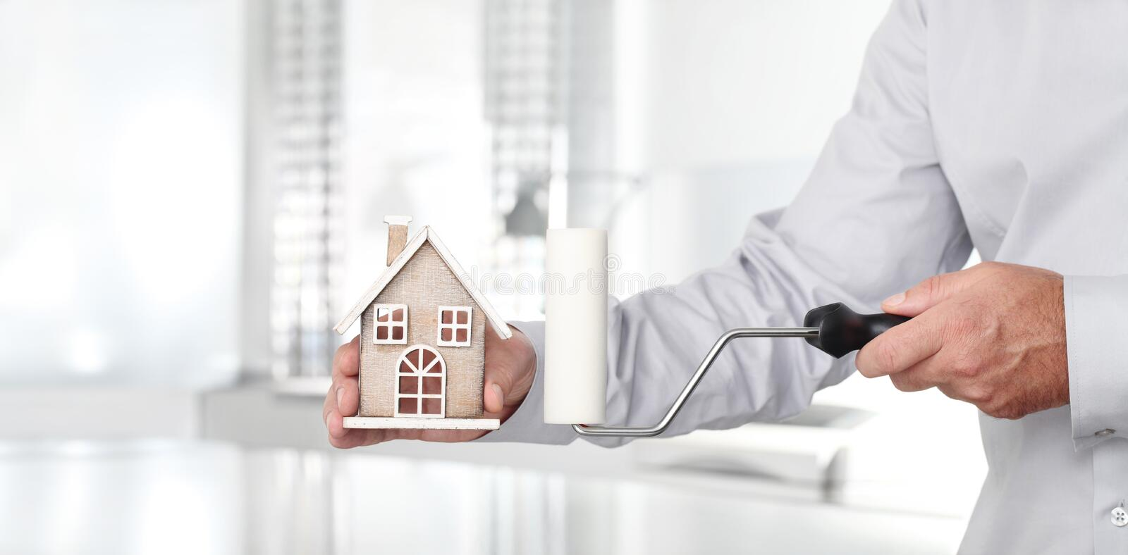 Hands with house and paint roller, home services concept stock photo