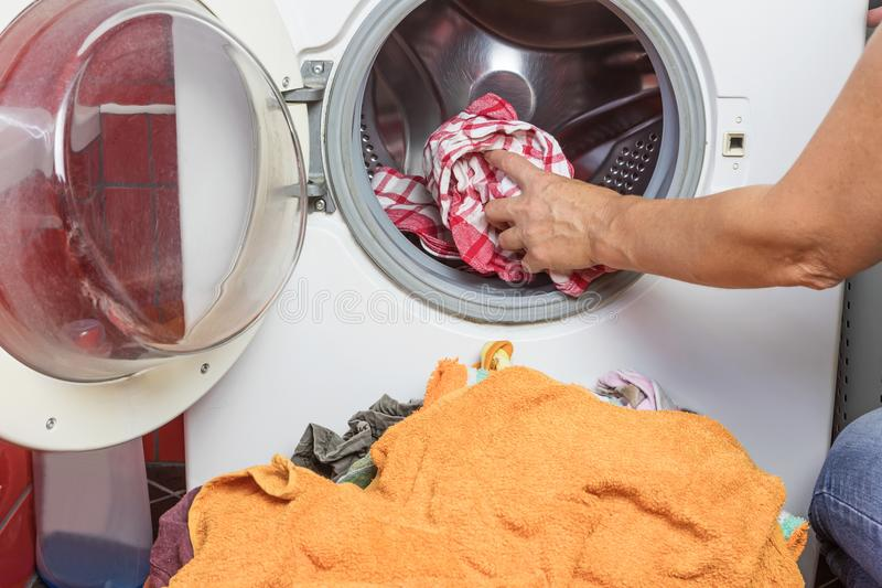 Housewife is putting dirty laundry in the washing machine stock photos