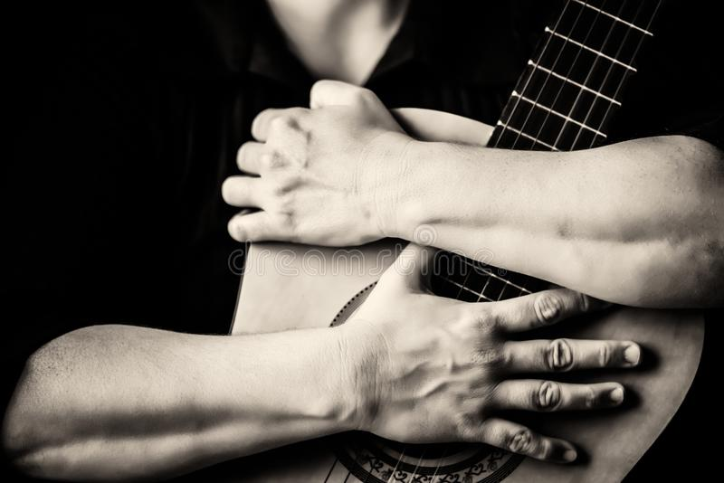 Hands hugging an acoustic guitar. Monochromatic on a black background royalty free stock image